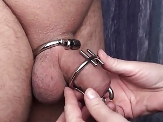 His cock is caged and teased by a mature woman