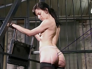 Hot brunette is tied up in a bard and fucked