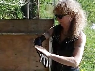 Leather wearing mistress prepares her fists for slaves ass BDSM