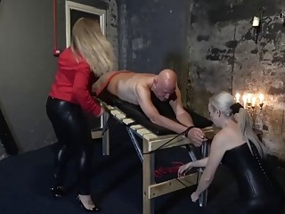 Bald dude tied up on the table and spanked by babes