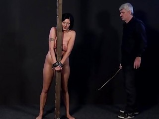 Two female slaves get their asses caned by their master