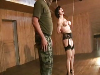 Pretty girl contorted in knots by freaky dungeon master BDSM